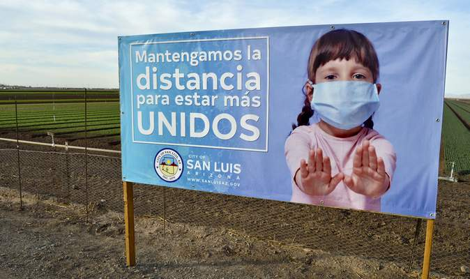 A City of San Luis, Ariz., sign encourages keeping a safe distance between people to prevent exposure to the COVID-19 virus during the ASU and Equality Health Foundation pilot program on Friday, Jan. 15, 2021. (Cesar Neyoy/The Yuma Sun via AP)
