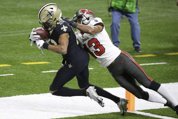 New Orleans Saints wide receiver Tre'Quan Smith, left, is hit by Tampa Bay Buccaneers defensive back Ross Cockrell (43) as Smith scores a touchdown during the second half of an NFL divisional round playoff football game, Sunday, Jan. 17, 2021, in New Orleans. (AP Photo/Butch Dill)