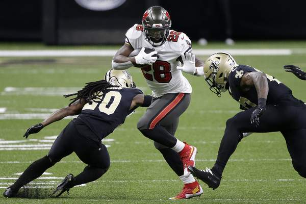 Tampa Bay Buccaneers running back Leonard Fournette (28) runs against the New Orleans Saints during the first half of an NFL divisional round playoff football game, Sunday, Jan. 17, 2021, in New Orleans. (AP Photo/Butch Dill)
