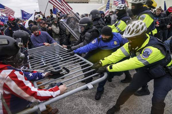 Associated Press During the Jan. 6 riot at the Capitol, crowds try to break through a police barrier.