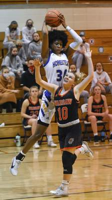 Mike Moore | The Journal Gazette Homestead junior Ayanna Patterson comes down with the rebound over Warsaw senior Kensie Ryman in the first period at Homestead High School on Tuesday.
