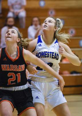 Mike Moore | The Journal Gazette Warsaw senior Audrey Grimm, left boxes out Homestead sophomore Allison Stephens in the first period at Homestead High School on Tuesday.