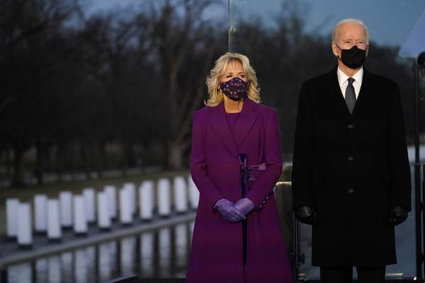 President-elect Joe Biden and Jill listen during a COVID-19 memorial, with lights placed around the Lincoln Memorial Reflecting Pool, Tuesday, Jan. 19, 2021, in Washington. (AP Photo/Alex Brandon)