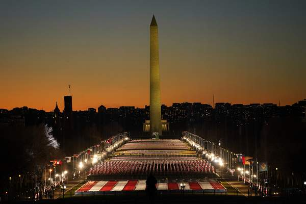 A field of flags is spread across the National Mall, with the Washington Monument in the background on Tuesday, Jan. 19, 2021, as seen from the West Front of the U.S. Capitol on the evening ahead of the 59th Presidential Inauguration in Washington. (AP Photo/Susan Walsh)