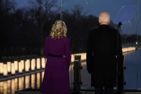 President-elect Joe Biden and his wife Jill Biden look out at lights during a COVID-19 memorial, with lights placed around the Lincoln Memorial Reflecting Pool, Tuesday, Jan. 19, 2021, in Washington. (AP Photo/Alex Brandon)