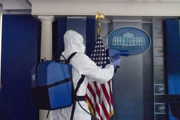 FILE - In this Oct. 5, 2020, file photo, a member of the cleaning staff sprays The James Brady Briefing Room of the White House, Monday, Oct. 5, 2020, in Washington. (AP Photo/Alex Brandon, File)