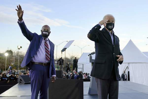 FILE - In this Monday, Jan. 4, 2021 file photo, President-elect Joe Biden, right, campaigns for Senate candidates Raphael Warnock, left, and Jon Ossoff, not pictured, in Atlanta. (AP Photo/Carolyn Kaster)