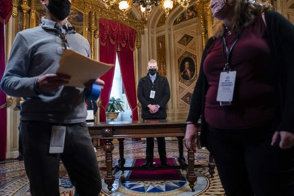 A stand-in for President-elect Joe Biden, center, stands in the President's Room of the U.S. Capitol during a rehearsal for the 59th Presidential Inauguration on Monday, Jan. 18, 2021, in Washington. (Jim Lo Scalzo/Pool via AP)