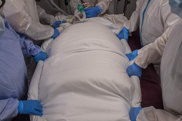 A medical team of the new Nurse Isabel Zendal Hospital prepares to rotate a patient at the COVID-19 ICU ward in Madrid, Spain, Monday, Jan. 18, 2021. (AP Photo/Bernat Armangue)