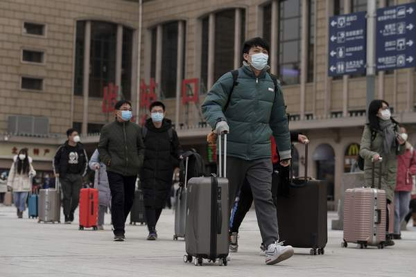 Passenger wearing face masks to help curb the spread of the coronavirus walk out from the Beijing railway station as they arrive in Beijing, Tuesday, Jan. 19, 2021. (AP Photo/Andy Wong)