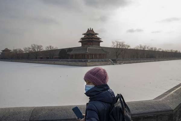 A visitor takes in the view from across the frozen moat of the Forbidden City during a snow day in Beijing Tuesday, Jan. 19, 2021. (AP Photo/Ng Han Guan)