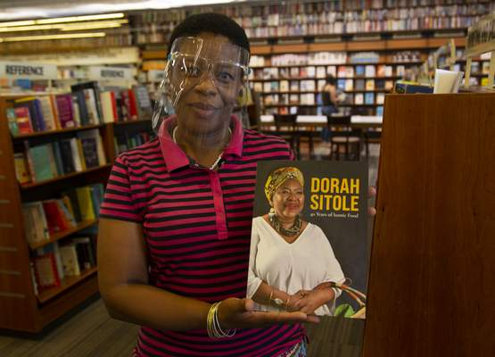 Book store worker, Dikeledi Nhlapo, holds a copy of Dorah Sitole's 40 Years of Iconic Food cook book in Exclusive Books in Hyde Park Corner, Johannesburg, Tuesday, Jan. 12, 2021. (AP Photo/Denis Farrell)