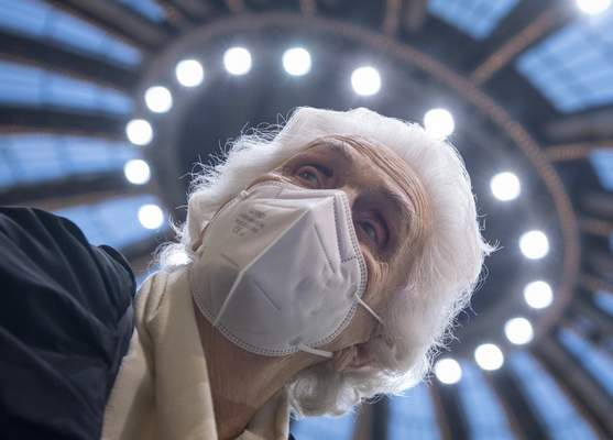After receiving her vaccination against the novel coronavirus, 90-year-old Odores H. sits under the domed roof of the vaccination centre in the Festhalle in Frankfurt, Tuesday, Jan. 19, 2021. (Boris Roessler/dpa via AP)