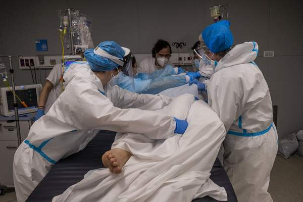 A medical team of the new Nurse Isabel Zendal Hospital rotates a patient at the COVID-19 ICU ward in Madrid, Spain, Monday, Jan. 18, 2021. (AP Photo/Bernat Armangue)