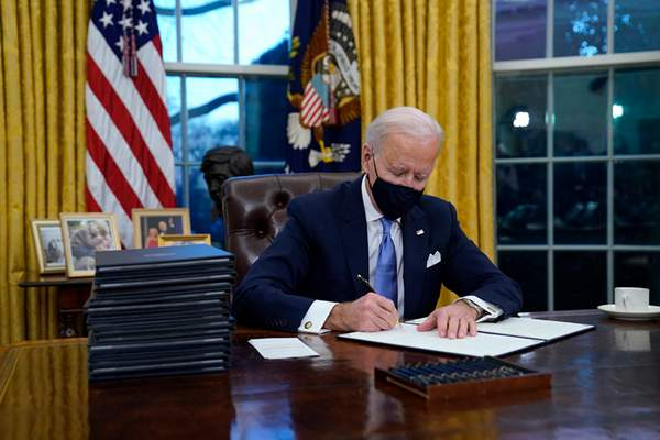 President Joe Biden signs his first executive order in the Oval Office of the White House on Wednesday, Jan. 20, 2021, in Washington.(AP Photo/Evan Vucci)