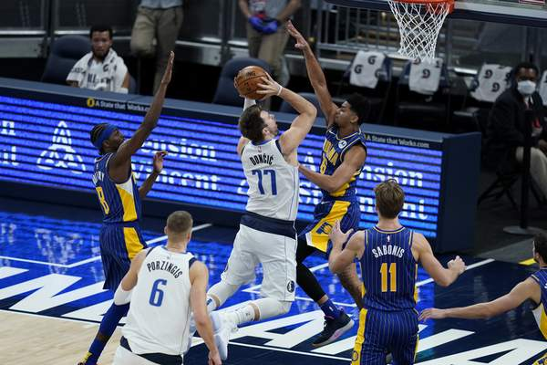 Dallas Mavericks' Luka Doncic (77) puts up a shot against Indiana Pacers' Jeremy Lamb (26) during the first half of an NBA basketball game, Wednesday, Jan. 20, 2021, in Indianapolis. (AP Photo/Darron Cummings)