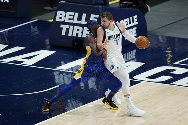 Dallas Mavericks' Luka Doncic (77) is defended by Indiana Pacers' Justin Holiday (8) during the first half of an NBA basketball game, Wednesday, Jan. 20, 2021, in Indianapolis. (AP Photo/Darron Cummings)