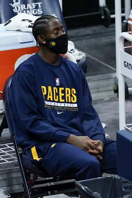 Indiana Pacers' Caris LeVert watches from the bench during the first half of an NBA basketball game against the Dallas Mavericks, Wednesday, Jan. 20, 2021, in Indianapolis. (AP Photo/Darron Cummings)