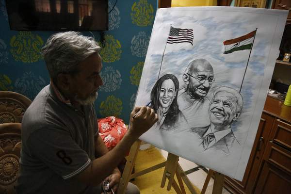 An Indian artist Aejaz Saiyed gives finishing touch to an art work featuring U.S.President-elect Joe Biden, Vice President-elect Kamala Harris and Indian freedom fighter Mahatma Gandhi, ahead of Biden's inauguration ceremony, in Ahmedabad, India, Wednesday, Jan. 20, 2021. (AP Photo/Ajit Solanki)