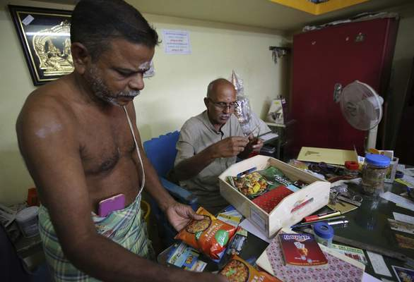A Hindu priest, left, and a temple official open a box full of packaged food and sweets sent by a non-government organization to be distributed among villagers ahead of the inauguration of U.S. Vice President-elect Kamala Harris, in Thulasendrapuram, the hometown of Harris' maternal grandfather, south of Chennai, Tamil Nadu state, India, Tuesday, Jan. 19, 2021. (AP Photo/Aijaz Rahi)