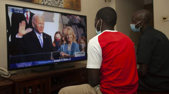 Kenyans watch President-elect Joe Biden's inauguration on the television, in Nairobi, Wednesday, Jan. 20 2021. Biden has officially become the 46th president of the United States. (AP Photo/Sayyid Abdul Azim)