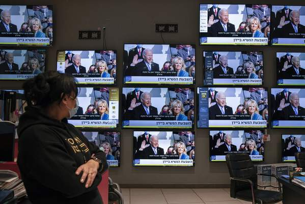 An Israeli electronics store employee looks at a wall of televisions broadcasting live the 59th U.S. Presidential Inauguration ceremony, in Ashkelon, Israel, Wednesday, Jan. 20, 2021. Biden became the 46th president of the United States on Wednesday. (AP Photo/Tsafrir Abayov)