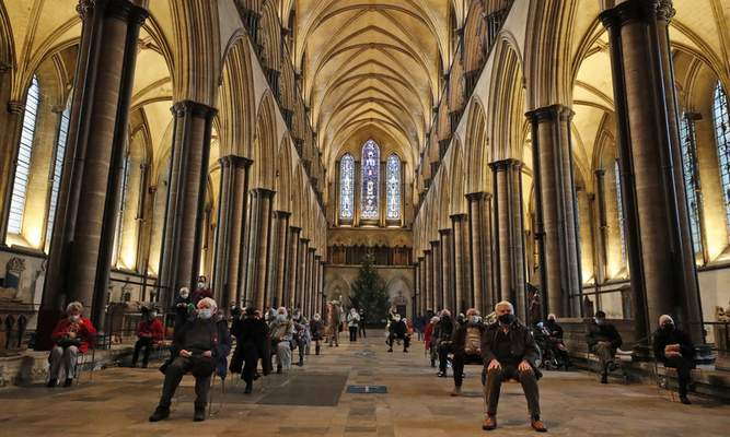 People sit and relax after receiving their Pfizer-BioNTech vaccination at Salisbury Cathedral in Salisbury, England, Wednesday, Jan. 20, 2021. (AP Photo/Frank Augstein)