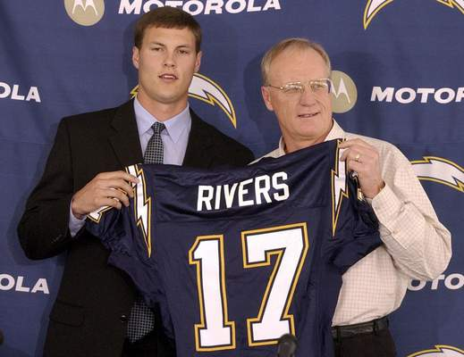 Rivers holds up his Chargers jersey with coach Marty Schottenheimer after being drafted fourth overall in 2004.