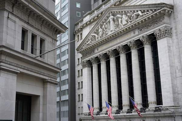 FILE - This Monday, Nov. 23, 2020 file photo shows the New York Stock Exchange, right, in New York.  (AP Photo/Seth Wenig)