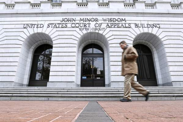 FILE - In this Jan. 7, 2015, file photo, a man walks in front of the 5th U.S. Circuit Court of Appeals in New Orleans. (AP Photo/Jonathan Bachman, File)