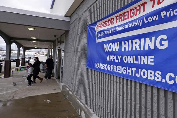 FILE - In this Dec. 10, 2020, file photo, a Now Hiring sign hangs on the front wall of a Harbor Freight Tools store in Manchester, N.H. The latest figures for jobless claims, issued Thursday, Jan. 14, 2021 by the Labor Department, remain at levels never seen until the virus struck. (AP Photo/Charles Krupa, File)