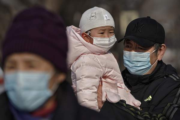 A man carries a child, both wearing face masks to help curb the spread of the coronavirus, as they stroll along a street near the popular frozen Houhai Lake in Beijing, Thursday, Jan. 21, 2021. (AP Photo/Andy Wong)