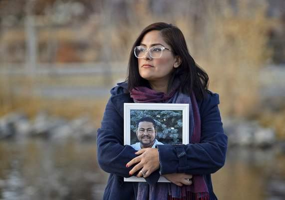 FILE - In this Dec. 15, 2020, file photo, Brenda Bravo Torres stands at a park in Reno, Nev., holding a photograph of her husband Miguel Angel Lopez Villal Pinzon who died of COVID-19 in August 2020. (Andy Barron/The Reno Gazette-Journal via AP, File)