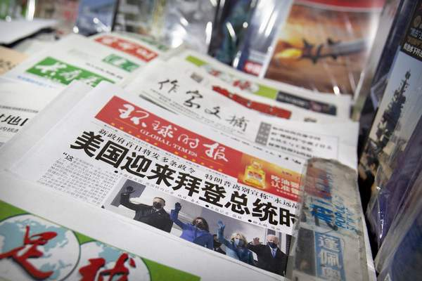 A copy of the Chinese state-run Global Times newspaper with a front page devoted to coverage of the inauguration of President Joe Biden is displayed at a newsstand in Beijing, Thursday, Jan. 21, 2021. (AP Photo/Mark Schiefelbein)