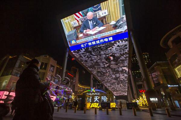 A vendor selling lighted balloons stands near a large video showing a government news report about the inauguration of President Joe Biden at a shopping mall in Beijing, Thursday, Jan. 21, 2021. (AP Photo/Mark Schiefelbein)