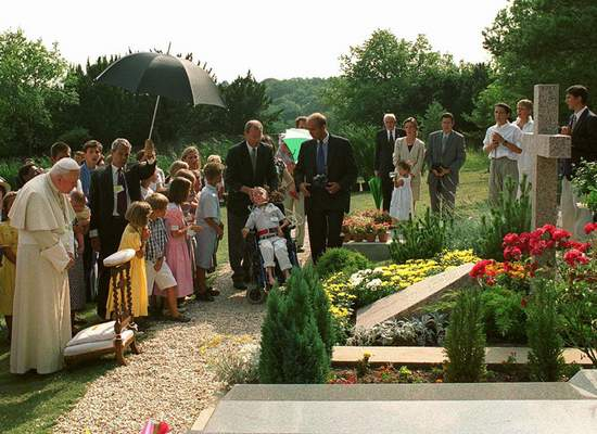 FILE - In this Aug.22, 1997 file photo, Pope John Paul II meditates by the grave of his former friend geneticist Jerome Lejeune, during a private visit to the Chalo-Saint-Mars cemetery near Paris. (AP Photo/Arturo Mari/file)