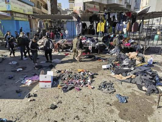 People and security forces gather at the site of a deadly bomb attack in a market selling used clothes, Iraq, Thursday, Jan. 21, 2021. (AP Photo/Hadi Mizban)