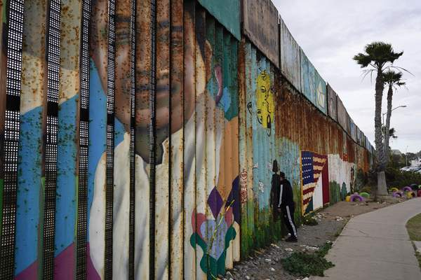 Associated Press In Tijuana, Mexico, this week, a man looks into San Diego through a wall at the U.S. border.