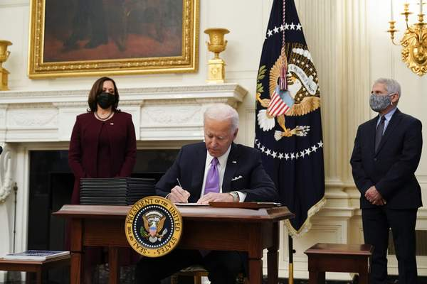 Associated Press President Joe Biden signs executive orders after speaking about the coronavirus, accompanied by Vice President Kamala Harris and Dr. Anthony Fauci, director of the National Institute of Allergy and Infectious Diseases.