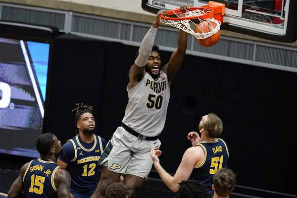 Purdue forward Trevion Williams (50) dunks over Michigan forward Austin Davis (51) during the first half of an NCAA college basketball game in West Lafayette, Ind., Friday, Jan. 22, 2021. (AP Photo/Michael Conroy)