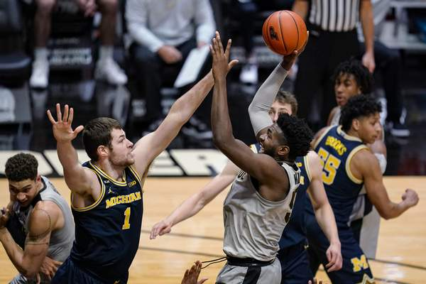 Purdue forward Trevion Williams (50) shoots over Michigan center Hunter Dickinson (1) during the second half of an NCAA college basketball game in West Lafayette, Ind., Friday, Jan. 22, 2021. (AP Photo/Michael Conroy)