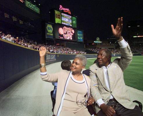 Major League Baseball's all-time career home run record holder Hank Aaron and his wife Billye take a lap in a golf cart around Turner Field in Atlanta, Thursday, April, 8, 1999, after a ceremony to mark the 25th anniversary of his breaking Babe Ruth's record of 714 home runs on April 8, 1974. (AP Photo/John Bazemore)