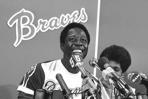 Obit Aaron Baseball FILE - Atlanta Braves' Hank Aaron smiles during a press conference at Atlanta Stadium, Ga., after the game in which he hit his 715th career home, in this April 8, 1974, file photo. With him is his wife Billye, partially obscured. Hank Aaron, who endured racist threats with stoic dignity during his pursuit of Babe Ruth's home run record and gracefully left his mark as one of baseball's greatest all-around players, died Friday. He was 86. The Atlanta Braves, Aaron's longtime team, said he died peacefully in his sleep. No cause was given. (AP Photo/File) (BJ STF)