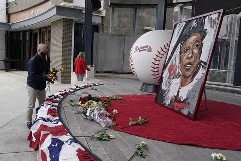 Obit Aaron Baseball Associated Press Atlanta Braves employees place flowers next to a portrait of Hank Aaron outside Truist Park on Friday. Aaron, who broke Babe Ruth's career home run record while playing for the Braves in 1974, died Friday.  (John BazemoreSTF)