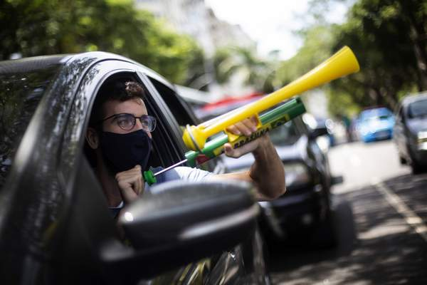 """Associated Press A demonstrator shouts """"Out Bolsonaro"""" while using a noisemaker during a caravan Saturday in Rio de Janeiro to protest the government's handling of the COVID-19 pandemic and demand the impeachment of Brazilian President Jair Bolsonaro."""