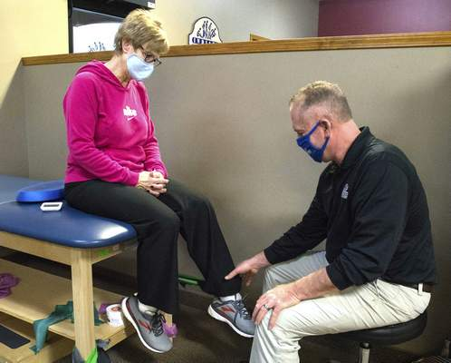 Troy Smith, co-owner and physical therapist at Indiana Physical Therapy, works with Jan Miller during her physical therapy session.