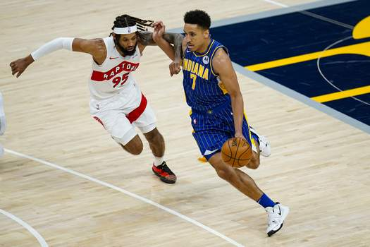 Raptors Pacers Basketball Indiana Pacers guard Malcolm Brogdon (7) drives on Toronto Raptors forward DeAndre' Bembry (95) during the first half of an NBA basketball game in Indianapolis, Sunday, Jan. 24, 2021. (AP Photo/Michael Conroy) (Michael Conroy STF)