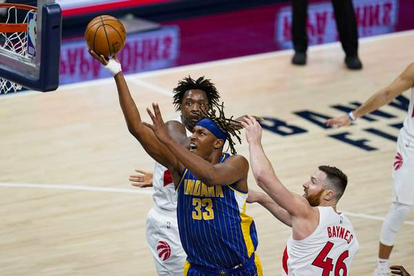 Indiana Pacers center Myles Turner (33) shoots between Toronto Raptors center Aron Baynes (46) and forward OG Anunoby (3) during the first half of an NBA basketball game in Indianapolis, Sunday, Jan. 24, 2021. (AP Photo/Michael Conroy)