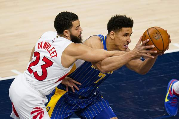 Toronto Raptors guard Fred VanVleet (23) defends against Indiana Pacers guard Malcolm Brogdon (7) during the first half of an NBA basketball game in Indianapolis, Sunday, Jan. 24, 2021. (AP Photo/Michael Conroy)