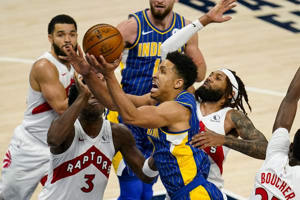 Indiana Pacers guard Malcolm Brogdon (7) shoots over Toronto Raptors forward OG Anunoby (3) during the first half of an NBA basketball game in Indianapolis, Sunday, Jan. 24, 2021. (AP Photo/Michael Conroy)